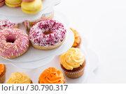 Купить «close up of glazed donuts and cupcakes on stand», фото № 30790317, снято 6 июля 2018 г. (c) Syda Productions / Фотобанк Лори