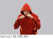 Купить «man in red hoodie fighting with fists or boxing», фото № 30790381, снято 3 февраля 2019 г. (c) Syda Productions / Фотобанк Лори