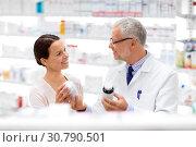 Купить «apothecary and woman with drug at pharmacy», фото № 30790501, снято 27 июня 2015 г. (c) Syda Productions / Фотобанк Лори