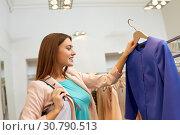 Купить «happy woman choosing clothes at clothing store», фото № 30790513, снято 19 февраля 2016 г. (c) Syda Productions / Фотобанк Лори