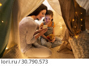Купить «happy family with smartphone in kids tent at home», фото № 30790573, снято 27 января 2018 г. (c) Syda Productions / Фотобанк Лори