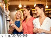 Купить «happy women pouring wine from dispenser at bar», фото № 30790609, снято 25 июня 2018 г. (c) Syda Productions / Фотобанк Лори