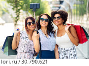 Купить «women with shopping bags taking selfie outdoors», фото № 30790621, снято 22 июля 2018 г. (c) Syda Productions / Фотобанк Лори