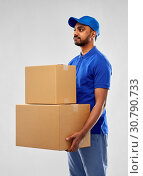 Купить «indian delivery man with parcel boxes in blue», фото № 30790733, снято 12 января 2019 г. (c) Syda Productions / Фотобанк Лори