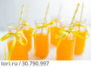 Купить «orange juice in glass bottles with paper straws», фото № 30790997, снято 6 июля 2018 г. (c) Syda Productions / Фотобанк Лори