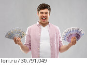 Купить «happy young man with fans of euro and dollar money», фото № 30791049, снято 3 февраля 2019 г. (c) Syda Productions / Фотобанк Лори