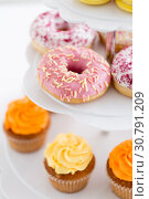 Купить «close up of glazed donuts and cupcakes on stand», фото № 30791209, снято 6 июля 2018 г. (c) Syda Productions / Фотобанк Лори