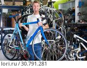 Купить «Portrait of positive male cyclist customer holding bicycle», фото № 30791281, снято 17 июля 2017 г. (c) Яков Филимонов / Фотобанк Лори