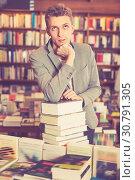 Купить «Pensive young man posing on stack of books in bookstore», фото № 30791305, снято 18 января 2018 г. (c) Яков Филимонов / Фотобанк Лори