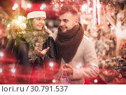 Купить «young couple in Christmas hat buying decoration at fair», фото № 30791537, снято 14 декабря 2017 г. (c) Яков Филимонов / Фотобанк Лори
