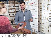Купить «Seller helping woman to choose door handles», фото № 30791561, снято 5 апреля 2017 г. (c) Яков Филимонов / Фотобанк Лори