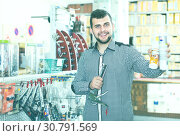 Купить «positive male customer examining various glue tubes in store», фото № 30791569, снято 5 апреля 2017 г. (c) Яков Филимонов / Фотобанк Лори