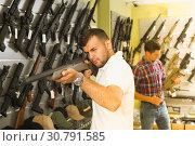 Купить «Friends choosing air-powered gun», фото № 30791585, снято 4 июля 2017 г. (c) Яков Филимонов / Фотобанк Лори