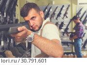 Купить «Portrait of adult man which is choosing air-powered gun», фото № 30791601, снято 4 июля 2017 г. (c) Яков Филимонов / Фотобанк Лори
