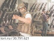 Купить «Young guys in military equipment with rifle in airsoft shop», фото № 30791621, снято 4 июля 2017 г. (c) Яков Филимонов / Фотобанк Лори
