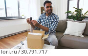 Купить «male blogger taking smartphone out of parcel box», видеоролик № 30791717, снято 26 апреля 2019 г. (c) Syda Productions / Фотобанк Лори
