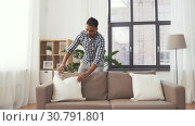 Купить «indian man arranging sofa cushions at home», видеоролик № 30791801, снято 27 апреля 2019 г. (c) Syda Productions / Фотобанк Лори