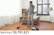 Купить «man with vacuum cleaner calling on cell at home», видеоролик № 30791821, снято 27 апреля 2019 г. (c) Syda Productions / Фотобанк Лори