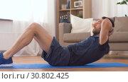 Купить «man making abdominal exercises at home», видеоролик № 30802425, снято 15 мая 2019 г. (c) Syda Productions / Фотобанк Лори