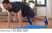Купить «man doing running plank exercise at home», видеоролик № 30802429, снято 15 мая 2019 г. (c) Syda Productions / Фотобанк Лори