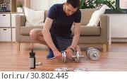 Купить «man assembling dumbbells at home», видеоролик № 30802445, снято 15 мая 2019 г. (c) Syda Productions / Фотобанк Лори