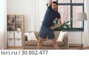 Купить «man exercising and leaning at home», видеоролик № 30802477, снято 15 мая 2019 г. (c) Syda Productions / Фотобанк Лори