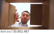 Купить «happy man opening parcel box», видеоролик № 30802481, снято 15 мая 2019 г. (c) Syda Productions / Фотобанк Лори