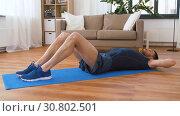 Купить «man making abdominal exercises at home», видеоролик № 30802501, снято 15 мая 2019 г. (c) Syda Productions / Фотобанк Лори
