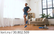 Купить «man with wireless earphones exercising at home», видеоролик № 30802509, снято 15 мая 2019 г. (c) Syda Productions / Фотобанк Лори