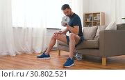 Купить «man exercising with dumbbells at home», видеоролик № 30802521, снято 15 мая 2019 г. (c) Syda Productions / Фотобанк Лори