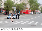 Купить «Tyumen, Russia, on May 9, 2019: Girls in short skirts cross the road on the crosswalk», фото № 30803205, снято 9 мая 2019 г. (c) Землянникова Вероника / Фотобанк Лори