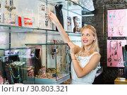 Купить «Portrait of young cheerful woman choosing earrings», фото № 30803321, снято 21 мая 2019 г. (c) Яков Филимонов / Фотобанк Лори