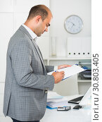 Businessman in office clothes filling up documents. Стоковое фото, фотограф Яков Филимонов / Фотобанк Лори