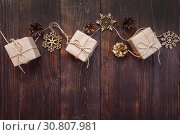 Christmas greetings card. Kraft gift boxes with rope and snowflakes, bumps on a wooden background with place for your text. Стоковое фото, фотограф Happy Letters / Фотобанк Лори