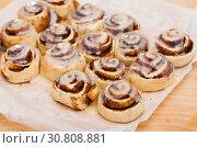 Купить «Cinnabons cinnamon rolls on baking paper», фото № 30808881, снято 15 июля 2020 г. (c) Яков Филимонов / Фотобанк Лори