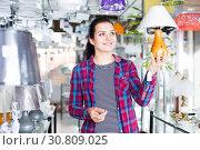 Купить «Woman looking for a stylish bedside lamp», фото № 30809025, снято 16 февраля 2017 г. (c) Яков Филимонов / Фотобанк Лори