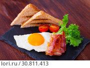 Купить «Fried eggs with bacon, toasted bread and tomatoes at plate, american breakfast», фото № 30811413, снято 23 мая 2019 г. (c) Яков Филимонов / Фотобанк Лори