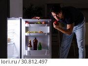 Купить «Man breaking diet at night near fridge», фото № 30812497, снято 8 февраля 2019 г. (c) Elnur / Фотобанк Лори