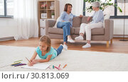 Купить «adults talking and girl drawing at home», видеоролик № 30813069, снято 12 мая 2019 г. (c) Syda Productions / Фотобанк Лори
