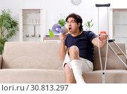 Купить «Leg injured young man suffering at home», фото № 30813297, снято 15 января 2019 г. (c) Elnur / Фотобанк Лори
