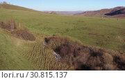 Купить «Hilly rural landscape with a herd of cows grazing in a meadow», видеоролик № 30815137, снято 4 мая 2019 г. (c) Serg Zastavkin / Фотобанк Лори