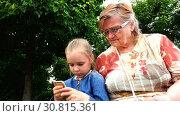 Купить «Granddaughter teaches grandmother to manage smart phone on touch screen», видеоролик № 30815361, снято 6 ноября 2017 г. (c) Aleksandr Sulimov / Фотобанк Лори