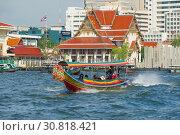 Туристическая лодка на фоне буддистского храма Wat Rakhang Khositaram Ворамахавихарн солнечным днем. Бангкок, Таиланд (2019 год). Редакционное фото, фотограф Виктор Карасев / Фотобанк Лори