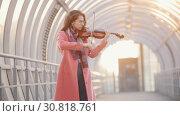 Купить «Young woman playing violin on the overhead passage», видеоролик № 30818761, снято 3 апреля 2020 г. (c) Константин Шишкин / Фотобанк Лори