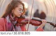 Купить «Charming young woman playing violin for free in public», видеоролик № 30818805, снято 22 февраля 2020 г. (c) Константин Шишкин / Фотобанк Лори
