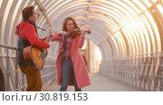 Купить «Woman with violin and man with guitar play together on the passage», видеоролик № 30819153, снято 3 апреля 2020 г. (c) Константин Шишкин / Фотобанк Лори