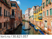 View of cityscape with colorful buildings on the banks of the canal and gondola with tourists, Venice, Italy (2017 год). Редакционное фото, фотограф Наталья Волкова / Фотобанк Лори