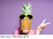 Купить «Fashion portrait woman and pineapple with sunglasses hiding head over color background», фото № 30833473, снято 13 мая 2019 г. (c) Евдокимов Максим / Фотобанк Лори