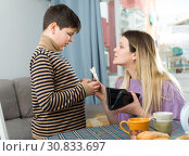 Portrait of young woman giving money to son, chatting at table. Стоковое фото, фотограф Яков Филимонов / Фотобанк Лори