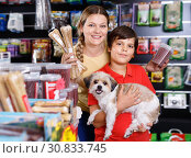 Купить «Cheerful woman with preteen son buying dog treats and chews in store to reward their precious pup», фото № 30833745, снято 22 августа 2018 г. (c) Яков Филимонов / Фотобанк Лори
